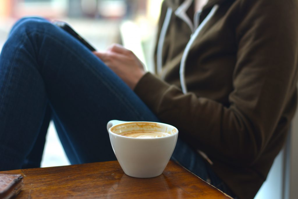 Someone quietly sitting with a cup of coffee.