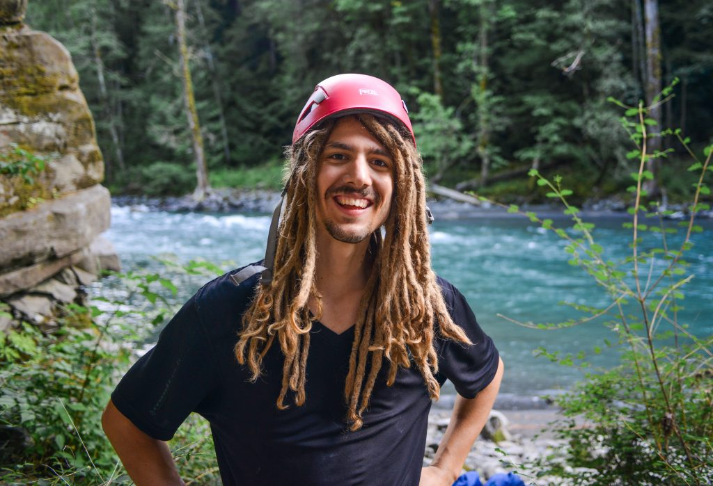 Andrew standing by a river in a forest